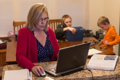 woman on laptop on kitchen counter with two boys playing in background