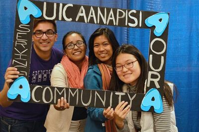 Asian students smiling holding a photo frame around their faces