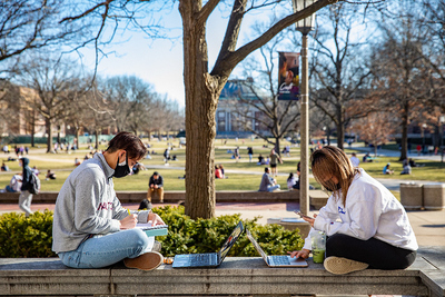 two masked students studying on the quad