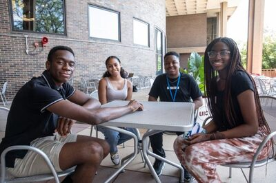 Four Black students smiling around a table