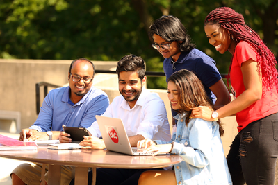 UIC students crowded around laptop at outdoor table