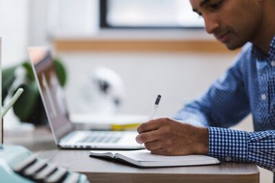 man working on laptop in home setting