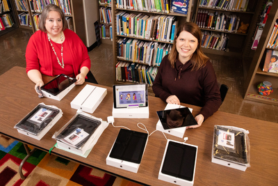 Sarah Isaacs, the librarian of the Early Intervention Clearinghouse, and research information specialist Jill Tompkins show some of the tablet computers and Wi-Fi hotspots available for loan
