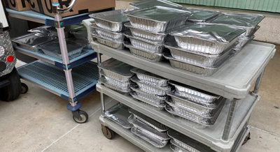 Covered foil tins of food stacked on rolling cart