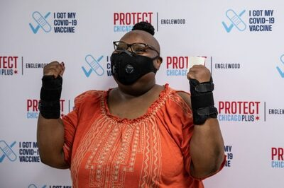 Lorraine Brown with arms in air and mask on celebrating vaccination