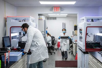 Scientists in the lab in white coats processing samples
