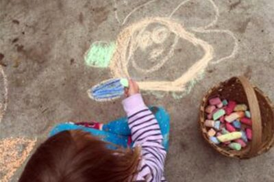 child drawing on sidewalk with colorful chalk