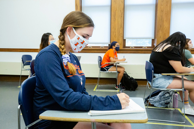 female student wearing Illini mask at desk in classroom