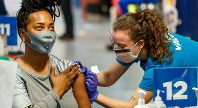 Female receiving vaccine from female nurse