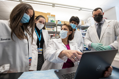 several masked, white coat lab workers gathered around a laptop in lab