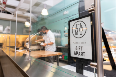 six feet apart sign in dining hall with worker
