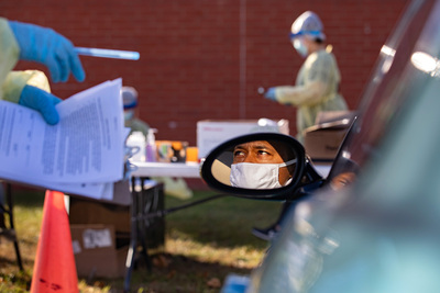 Patient in rear-view car mirror getting testing instructions
