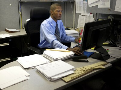 man in shirt and tie working at a desk on computer
