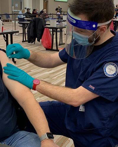 Jason Brooks administers COVID-19 vaccine