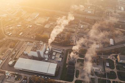 overhead view of factory in neighborhood emitting smoke from smokestacks