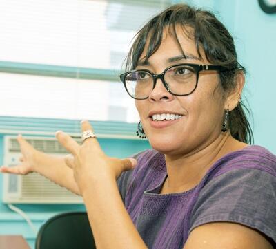 Woman in glasses talking in office