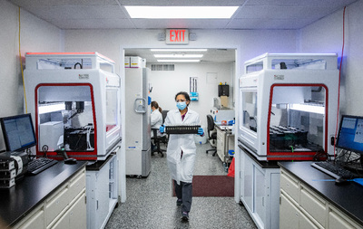 Researcher in SHIELD lab carrying samples