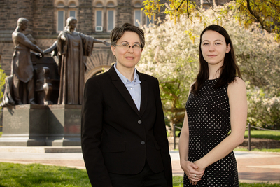 Female professor and female grad student pose in front of the Alma Mater on UIUC campus