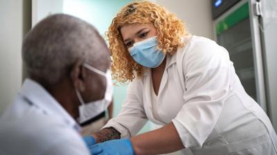 masked female healthcare worker assisting black male older patient in mask